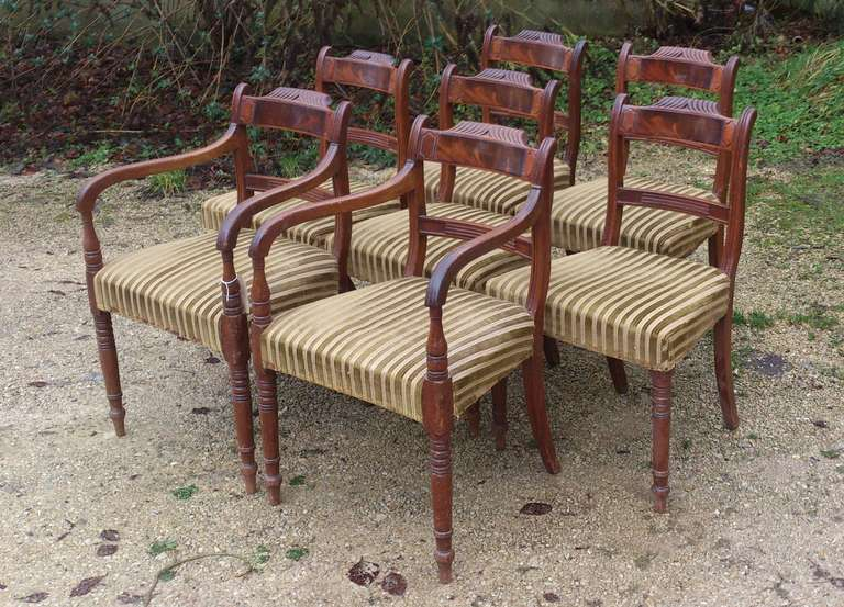 Pretty set of 8 Regency mahogany dining chairs, six singles and two armchairs. They are made of good solid mahogany with a flame mahogany section in the back rest. 