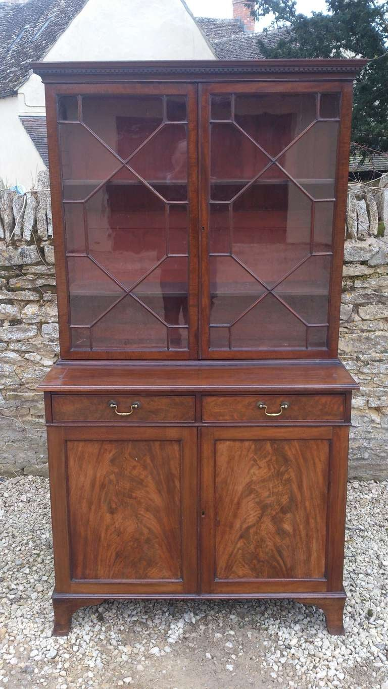 Unusually small mahogany bookcase with flame mahogany fronts on the lower doors and astral glazed upper doors with plum pudding mahogany frames, standing on splayed bracket feet. Please note the shrinkage split on the surface will be restored prior