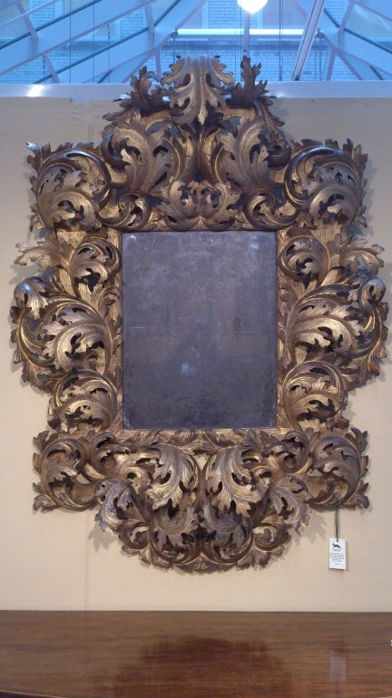 Very rare 17th century carved wood and gilded Rococo mirror with lovely old glass, the interesting thing about this mirror is the scale of the carving and the generosity of the form, quite theatrical and simply wonderful, Italian (probably Bologna)