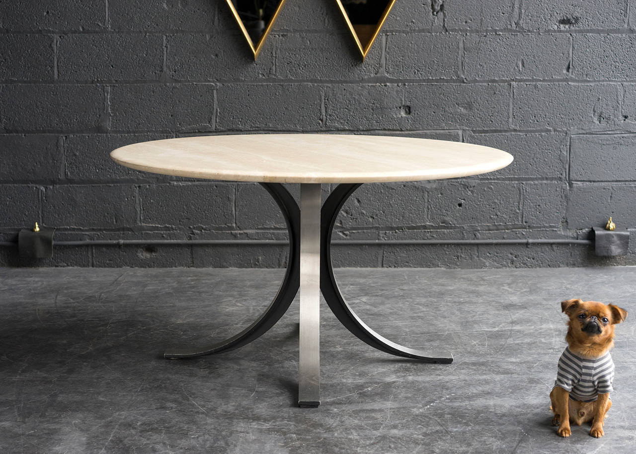 Here we have a nicely proportioned table which works comfortably with standard height dining chairs yet is slightly lower than a conventional height table. The base is constructed of heavy black metal with a stainless steel face. Cantilevered