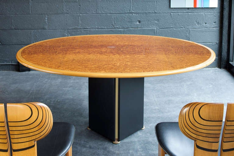 An oval shaped table with inset burl top and outer band with contrasting inlay of ebony and light walnut.