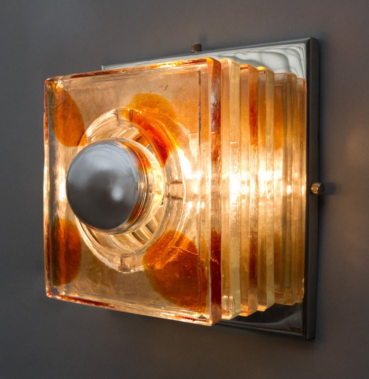 Four layers of two colored raw crystal supported by a stainless steel base and exposed mirrored lightbulb.