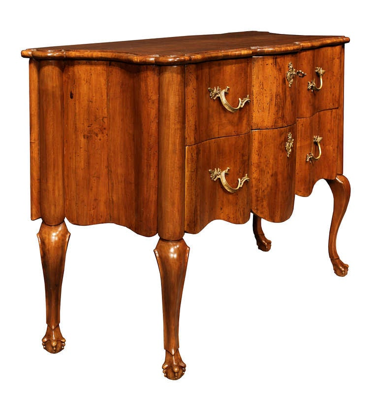 A very elegant Italian 18th century walnut Venetian commode. The commode is raised on scrolled legs in the shape of a ball and claw. The fine arbalette shaped frieze continues on all sides. Above two wide drawers with brass keyholes escutcheons and