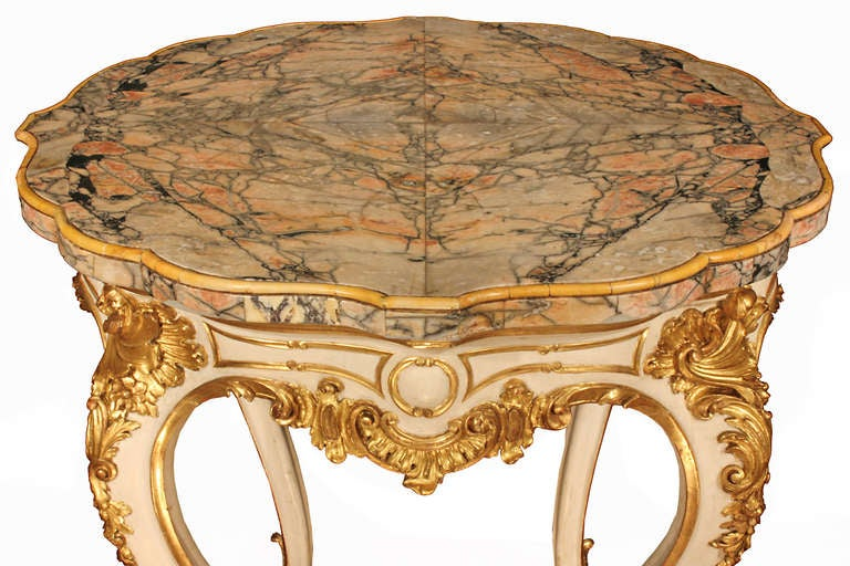 A stunning Italian early 19th century Louis XV st. patinated and gilt center table. The table is raised by very elegant slender cabriole legs decorated with richly carved gilt acanthus leaves and scrolls. On each side of the frieze is a central Oeil