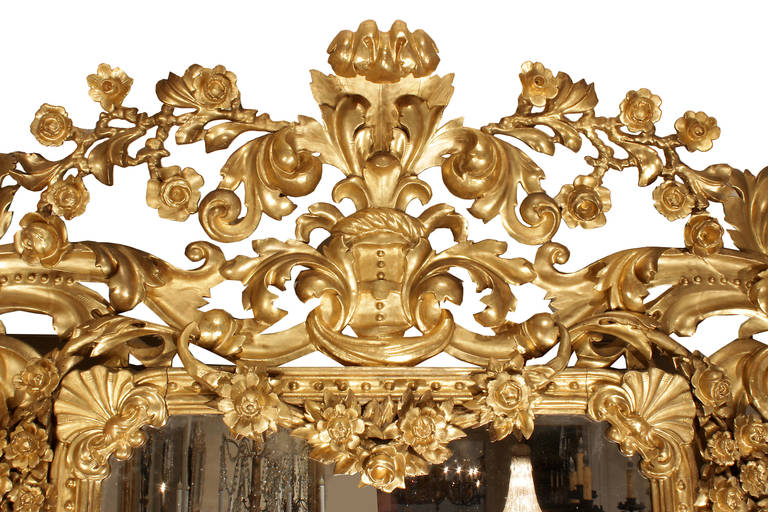 A sensational and large scale Italian 19th century Rococo style giltwood mirror. The richly carved frame is decorated with pierced scrolled acanthus leaves. The top central reserve is a Fleur de Lys spray flanked by floral garlands with carved