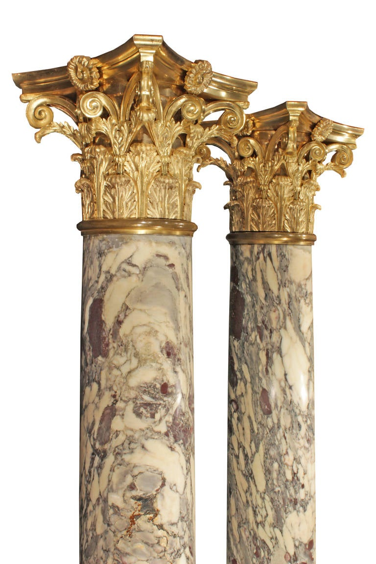 A spectacular pair of French 19th century marble and ormolu columns, signed Sormani. The Fleur de Pêcher marble columns are on a square base with a finely chased laurel wreath bottom band. At the top of each column is a magnificent Corinthian
