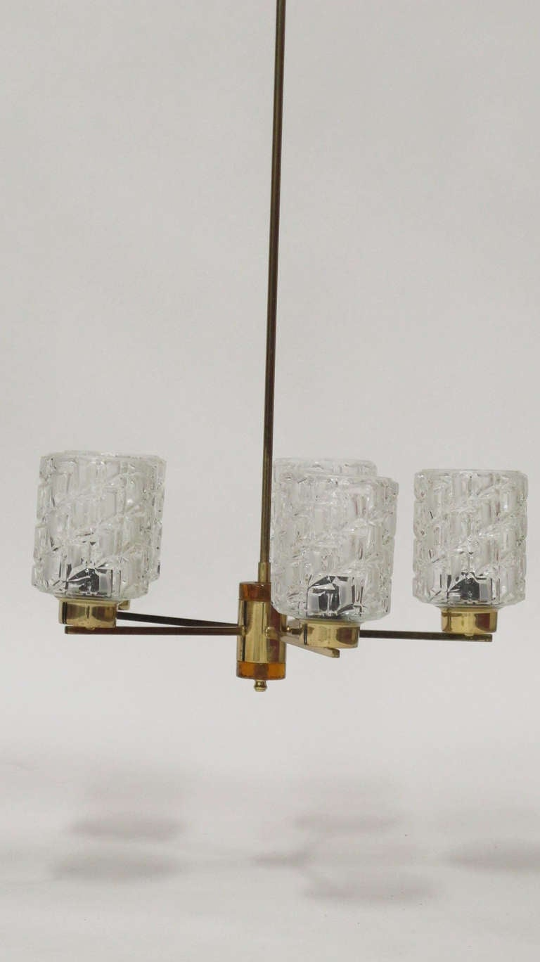 Carl Fagerlund for Orrefors six-light chandelier with amber glass center and brass arms. Measures: 33