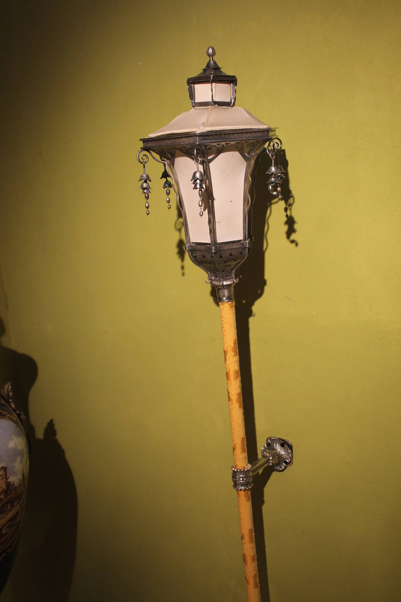 A beautiful venetian chiseled silvered metal processional wall lamp embellished with dangles. White silk pagoda shape shade. The wood pole is put in a silvered bronze support and is decorated with a yellow damask and can be easily wall