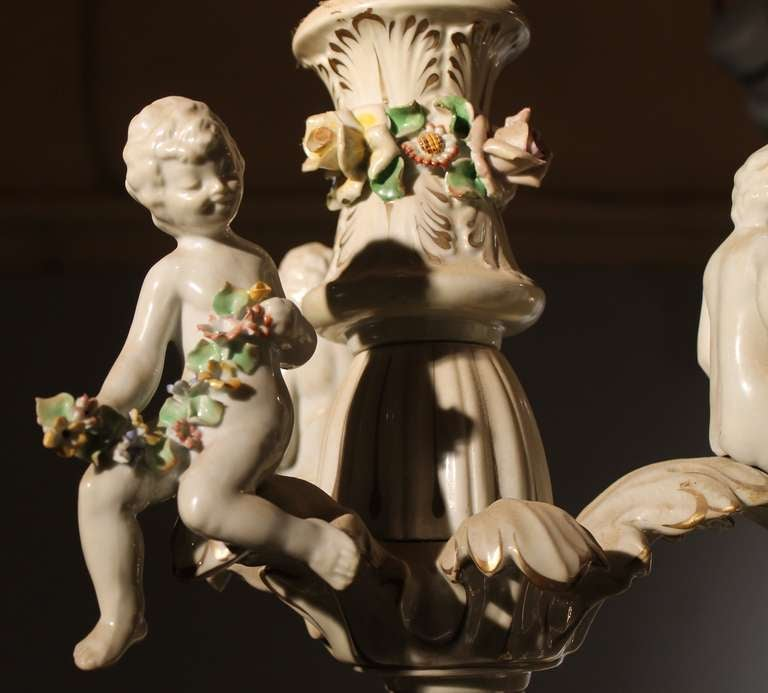 This magnificent antique 19th Century two-tiers porcelain chandelier has an exceptional quality. It was crafted by the renowned Italian Capodimonte pottery manufactory.  This enchanting white porcelain ceiling lamp features twelve lights (8 lights