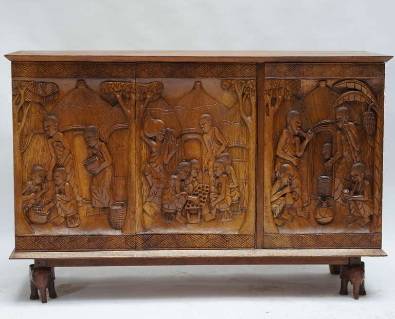 One of a kind ethnic wooden cabinet from the 1950s depicting rural life in Zaïre (now the Congo). Bas-relief technique on solid wood. Great original condition. The front legs of this cabinet have been shaped as little elephants. Will look good in