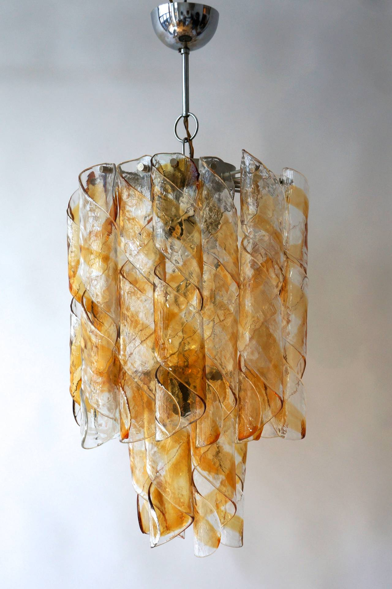 A wonderful confection in amber and clear curlicue Murano glass chandelier. 22 round Murano glass tubes. Four candelabra type bulbs. Any chain length and canopy can be provided upon request.  Measures: Total height 80 cm.