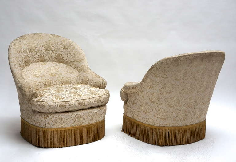 Two matching French nursing chairs from circa 1900, original white and cream upholstery with a floral motif, finished with a gold fringe. Please note that price is per item not for the set.