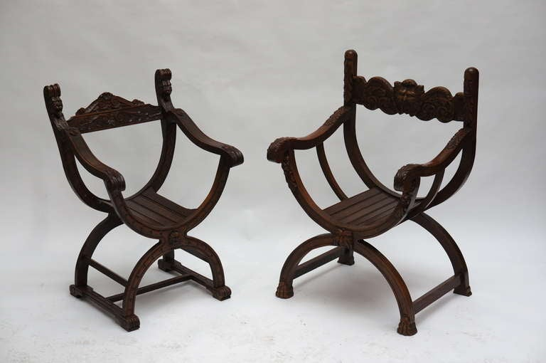 Renaissance style Savonarola style armchairs.  Set off two carved oak chairs from circa 1950s. One of these features a faun-like creature in the middle of the back of the seat. Great looking classical chairs that can be used in a modern setting as