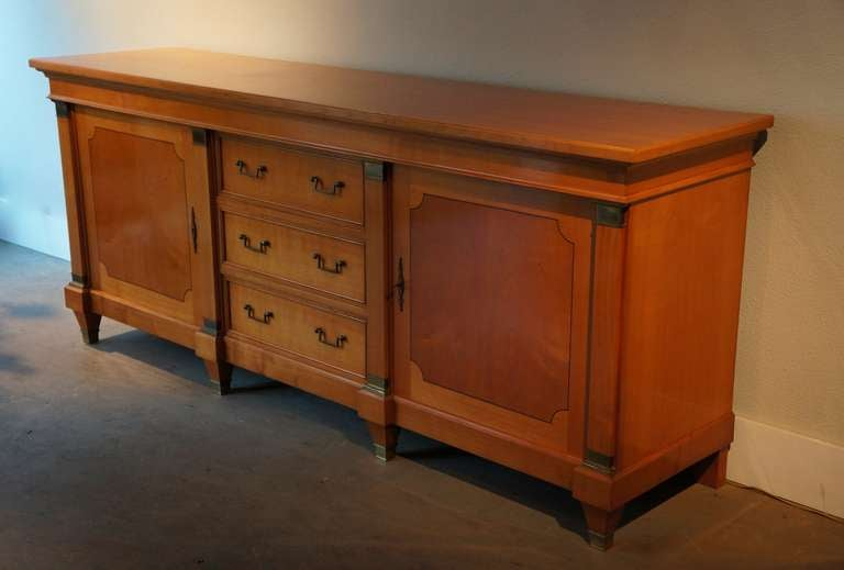 A nice sideboard with three drawers and two doors. Period: Early 1950s.  In good original condition with bronze details. Width:230 cm. Height:96 cm. Depth:56 cm.