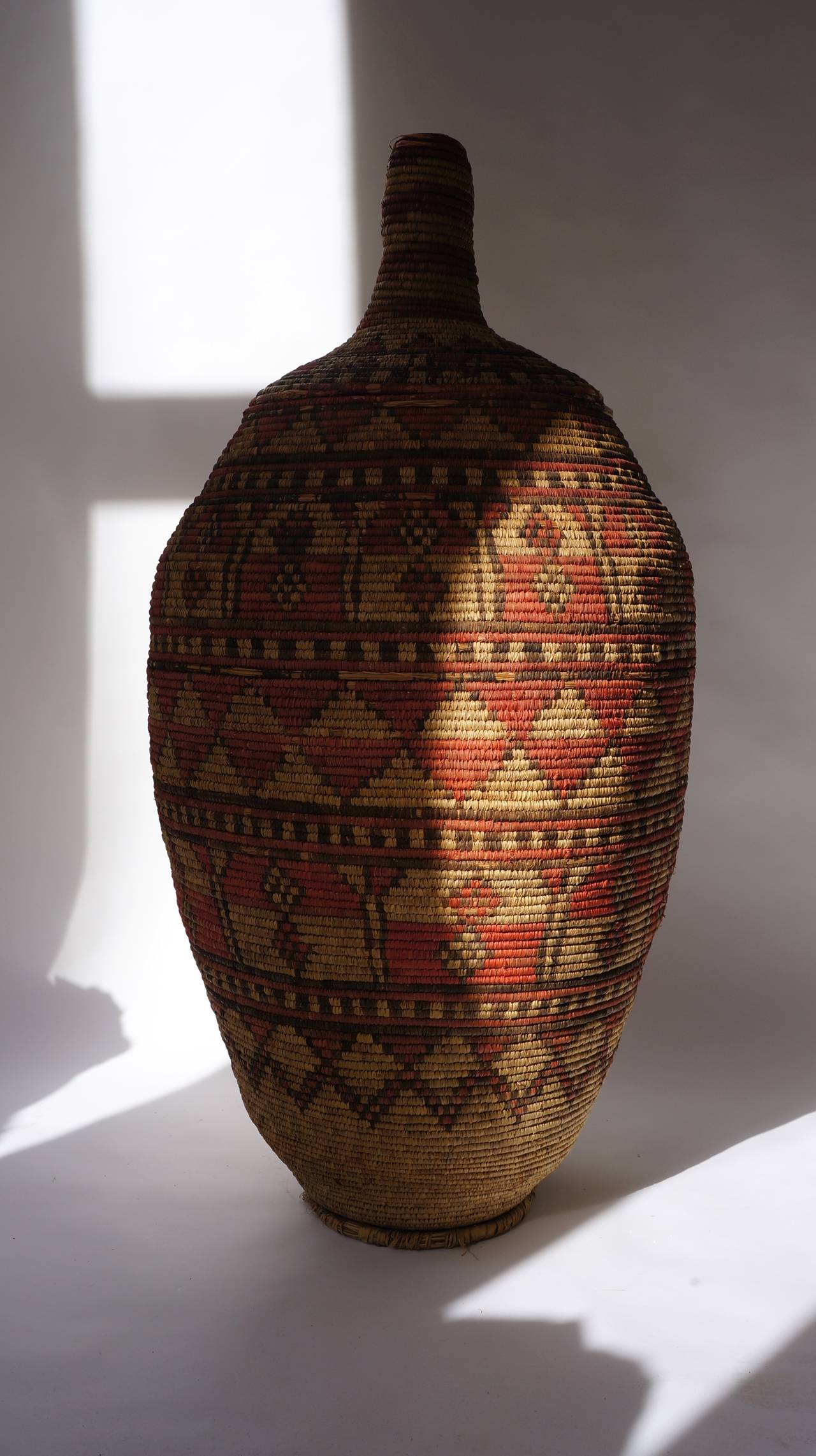 An impressive and seldom Nigerian large basket garment and cover, with dyed patterned band.