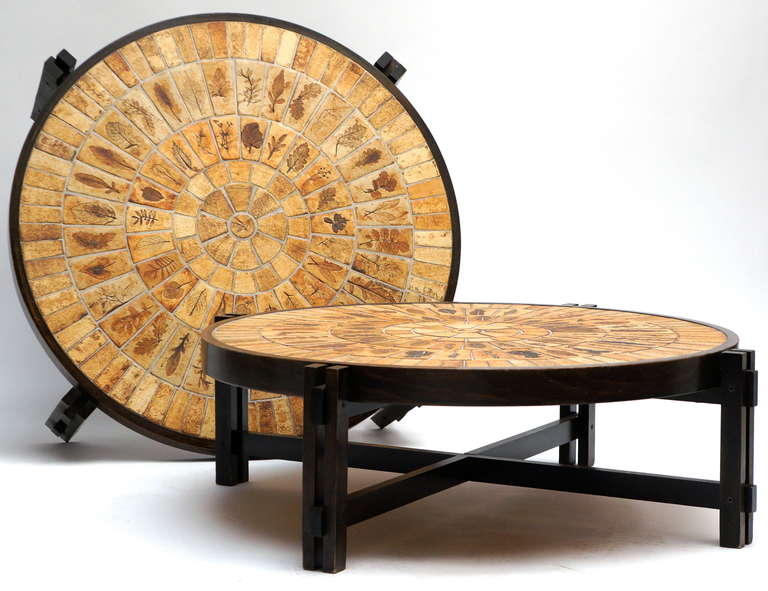 Two fantastic coffee tables by Roger Capron with an organic pattern of leaf pressed tiles in tones of brown, tan and beige. The base is lacquered wood.  Diameter 108 cm. Heigh 33 cm.