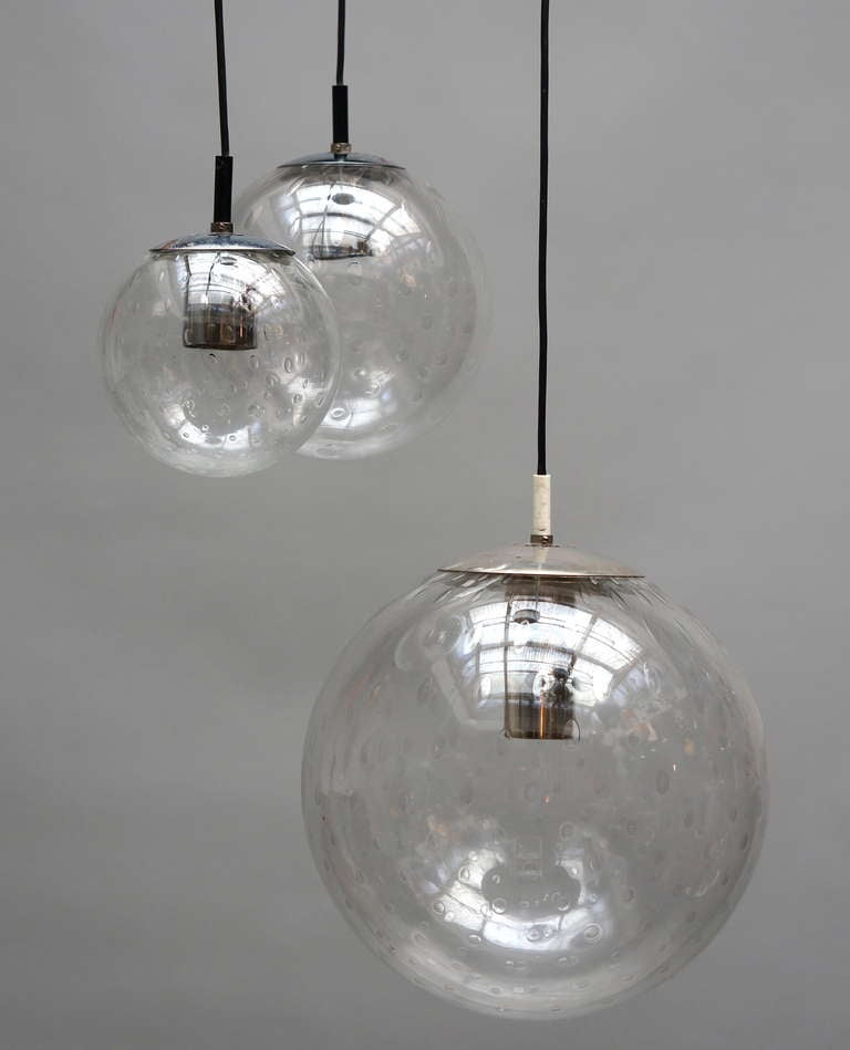 Three 'bubble' glass globes suspended at variant and adjustable lengths.