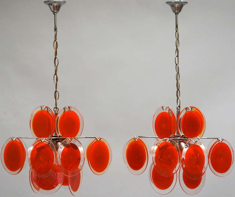 Two Vistosi chandeliers with three rows of nice clear red Murano glass discs. Chromed metal fixture. Diameter:35 cm. Height:70 cm.
