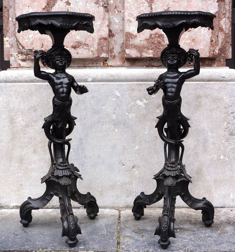 A charming pair of carved and blackened pearwood candle stands in the form of infant Blackamoor caryatids emerging from leafy scrolls and resting on voluted tripods. Napoleon III Style and period, circa 1860.