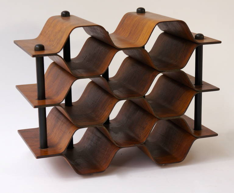 Beautiful wine rack designed by Torsten Johansson for AB Formtra¨ in Sweden, circa 1960.  The rack is made of beautiful quality deep brown tropical hardwood with metal horizontal supports. It's eye-catching shape resembles a honeycomb that holds up