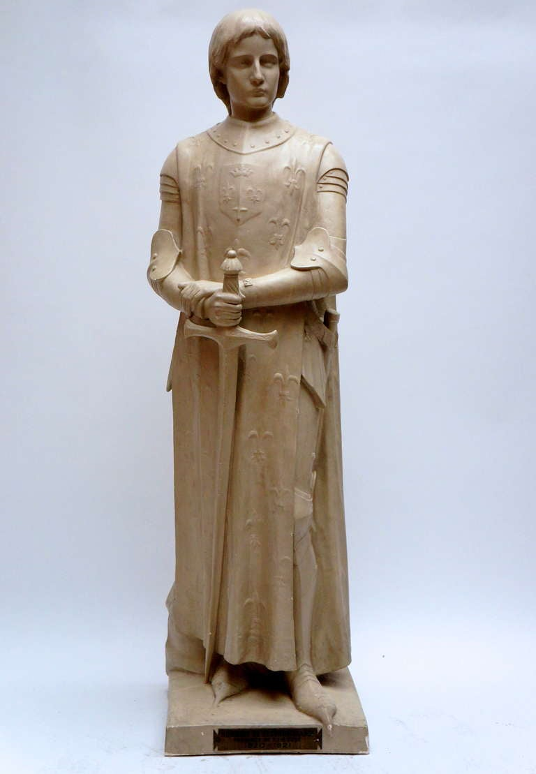 A life size plaster sculpture representing Jeanne of d'Arc as an androgynous girl dressed as a knight and wearing a fleur-de-lys covered cloak, holding a long sword in her hand. Sculpture by Andre Besqueut (French sculptor born 1850), presented at