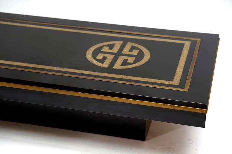 1970s Italian coffee table by De Nisco in wood covered with black melamine; top surface is an enameled metal plaque with the insertion of metal elements and is bound by a strip of gilded metal. Some oxidation on the metal strip. Normal wear