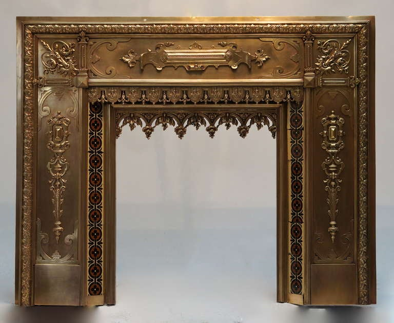 A bronze and brass fire surround, in the eclectic style of the late 19th century, incorporating very crisp Renaissance, Louis XIV and Gothic Revival motifs as well as enamel flower incrustations around the gate.  The dimensions of the interior