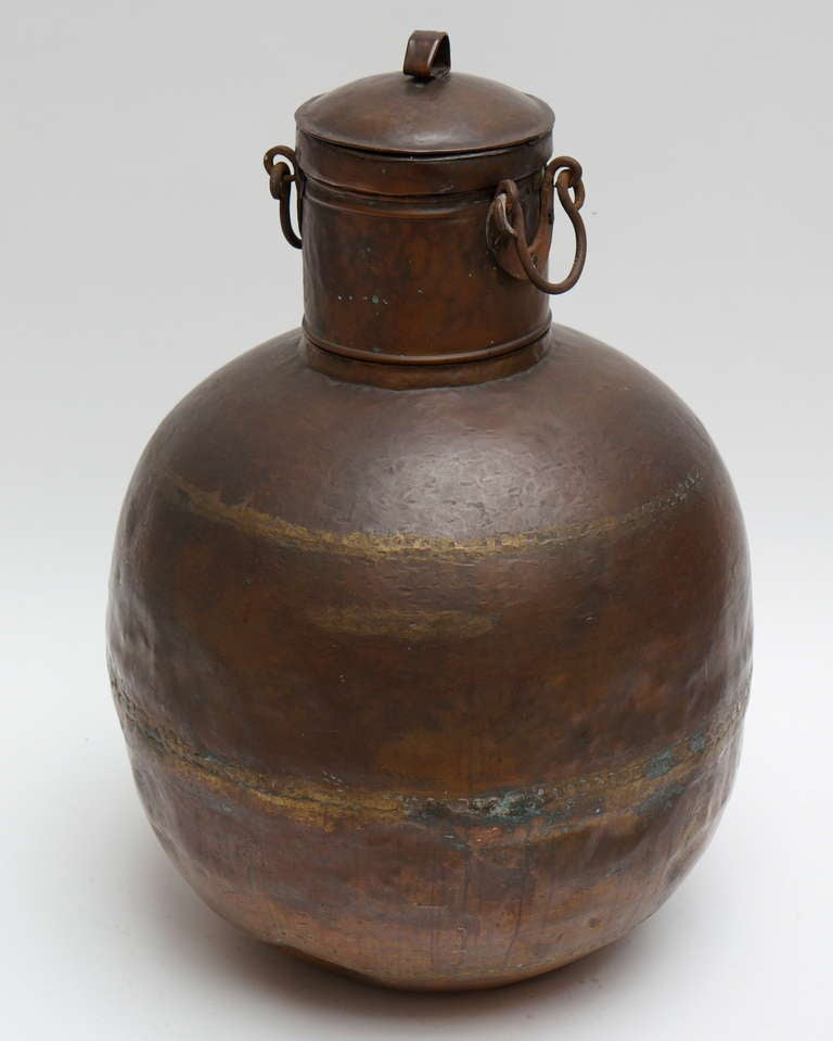 A tall copper covered container with two hinges at the neck.