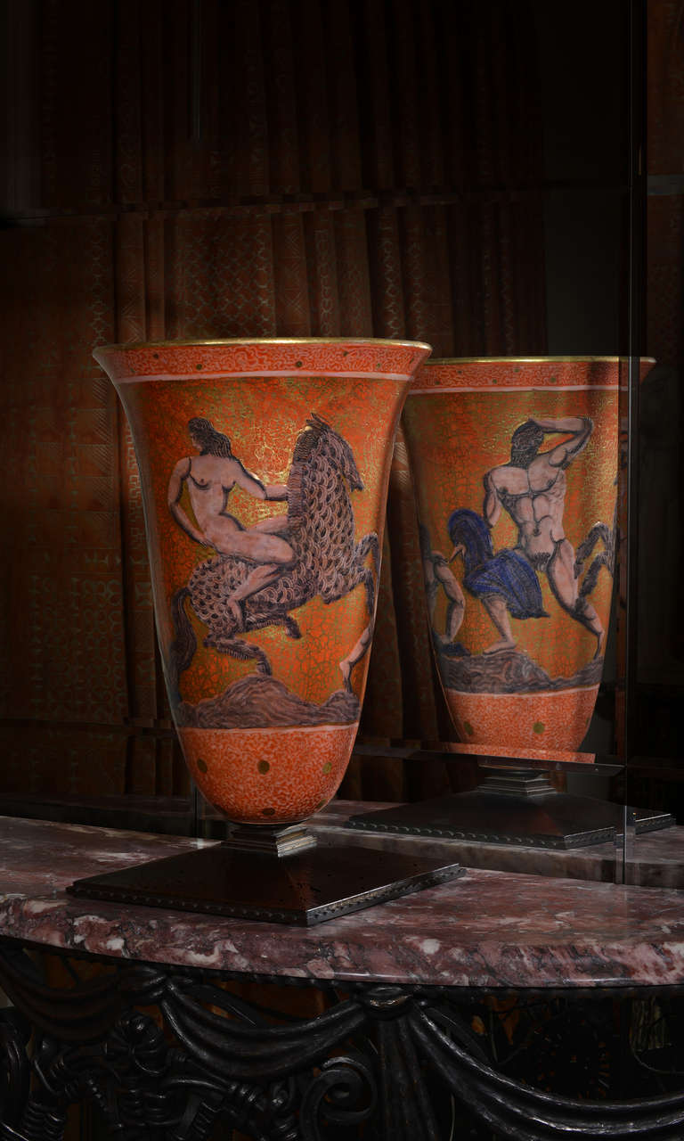 This magnificent ceramic urn is arguably the greatest work of Mayodon, exhibiting great artistry both as a ceramist and as a painter. It is decorated with a mythological theme with nude males and a rider on a horse on a rich orange and gold ground.