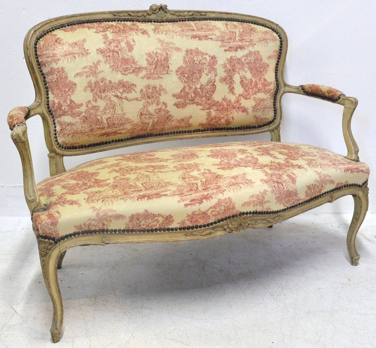 This elegant, small canape was carved in France, circa 1860. The antique banquette seating features delicate carvings around the frame, arm rests and cabriole legs. The love seat has been re-upholstered with a 19th century French red and beige