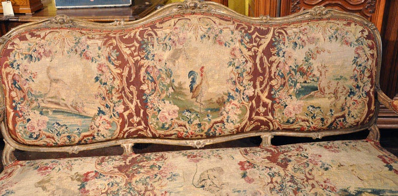 Exceptional antique Louis XV sofa from the annexes of the Chateau of Versailles in France, circa 1760. This wonderfully hand-carved eight-leg canapé with original gilt finish, features the 18th century Aubusson tapestry which has been restored to