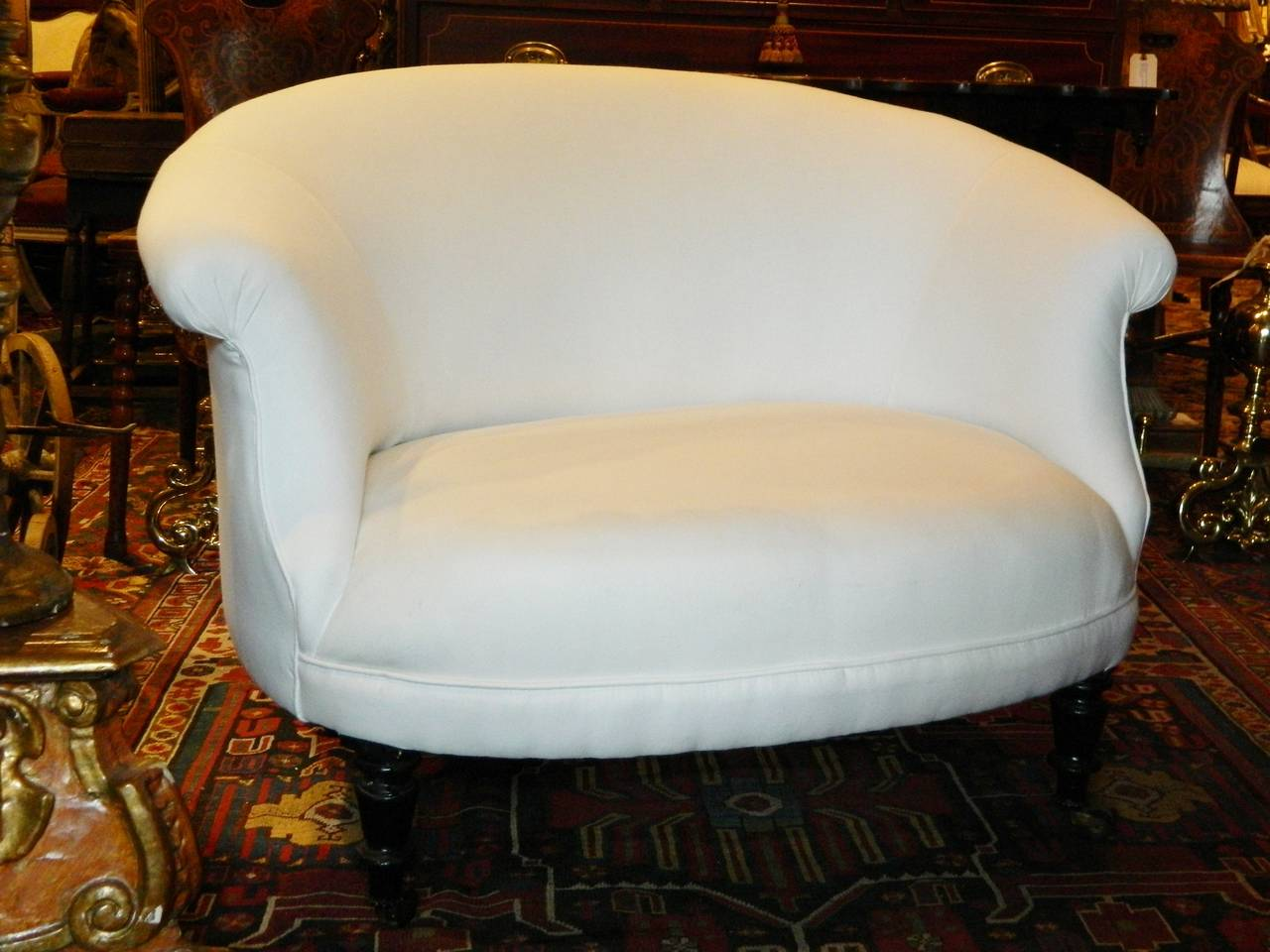 A French Napoleon III settee having continuous arched back raised on turned legs with casters, circa 1880. New muslin upholstery.