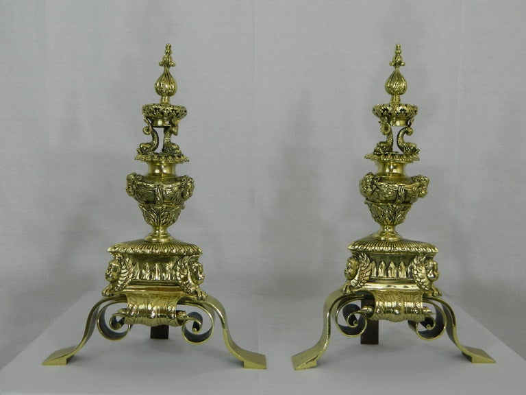 A unique pair of 19th century chenets or andirons beautifully decorated with urns, cherubs, dolphins, fleur-de-lys and a flame finial with a flame finial.