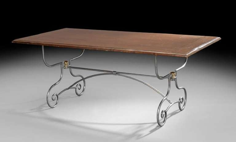 Early 20th century Spanish-style mahogany and silvered metal guard room table, the rectangular top with molded edge, raised on shaped and scrolling tubular end supports joined by stretchers and ending in scrolled feet.