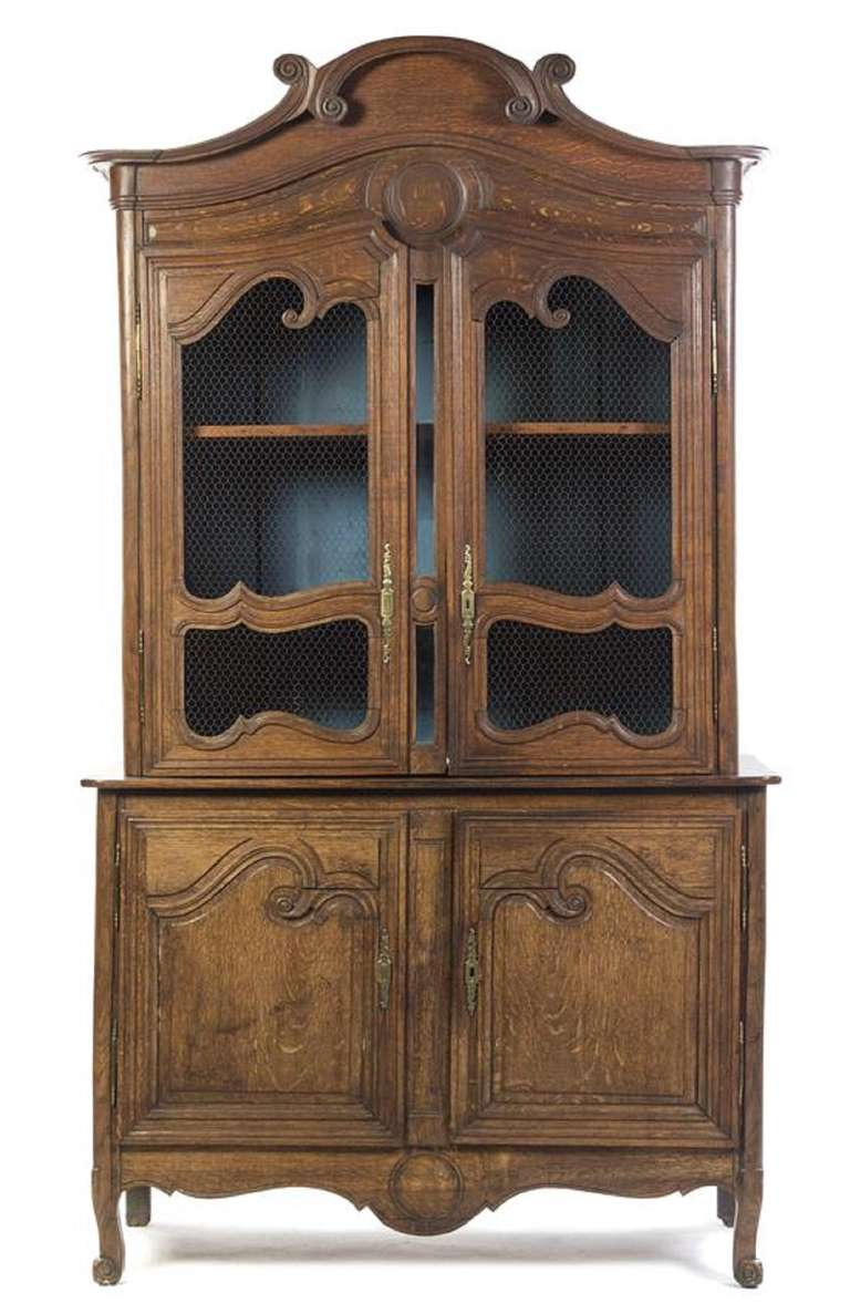 19th Century French Provincial Oak Buffet a Deux Corps, in two parts, the upper section having a domed cornice over two grill inset doors opening to a shelved interior, the lower section enclosing two cupboard doors, raised on scroll feet
