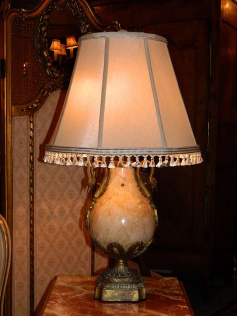 Empire style lamp made of hand polished beige marble with hand-forged bronze designs. The lamp has a central urn form held by a bronze pedestal. The lamp has extensive bronze features and details.