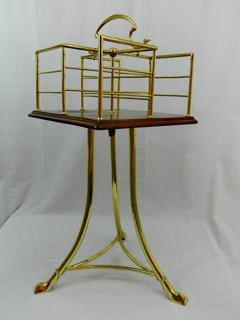 19th century English revolving mahogany and brass book stand or side table featuring a revolving top with a handle and four dividers supported by a tripod base.