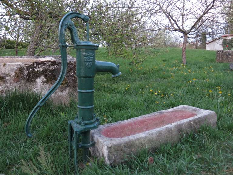 A French antique limestone fountain with handcrafted limestone basin with a water pump in iron hand finished.  Original, signed