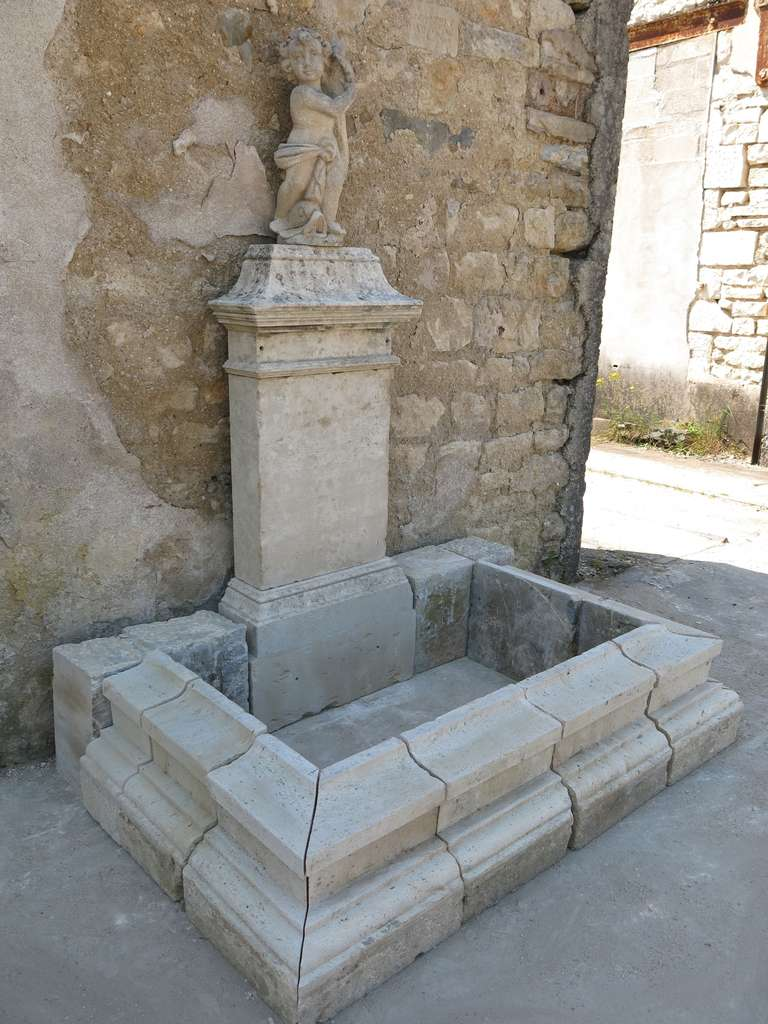 Rare french wall fountain in limestone, France. Composed of 17th-18th-19th century elements. Possible to extend the basin (more elements available).  The water falls from the head of the fish at the Cherubs legs statue, on the top of the