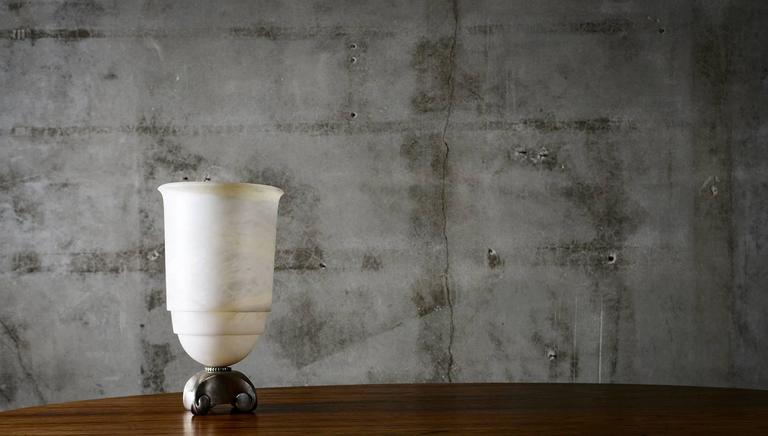 Evoking the heritage of French master craftsmen Emile-Jacques Ruhlmann, this lamp vase made from alabaster with silvered bronze base is notable for its classical simplicity crafted with the finest materials, harmonious proportions, architectural