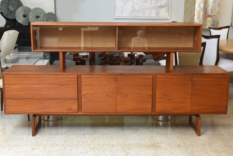 This Danish modern teak sideboard with superstructure by Bodil Kjaer was manufactured for E. Pedersen and Sons, circa 1950s. The piece comes with three compartments on a raised legs. The superstructure is elevated with two compartments for storage.