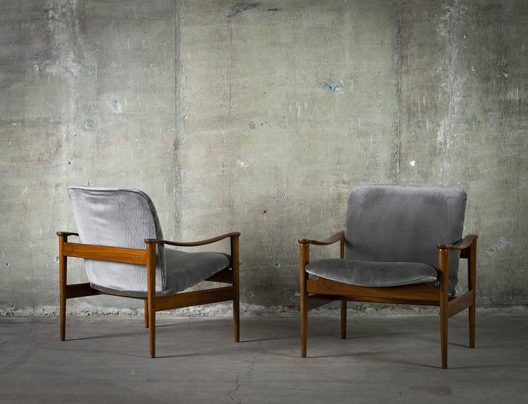 This pair of easy chairs is the work of Norwegian designer Fredrik Kayser. The piece is crafted from mahogany and suede, circa 1950s.