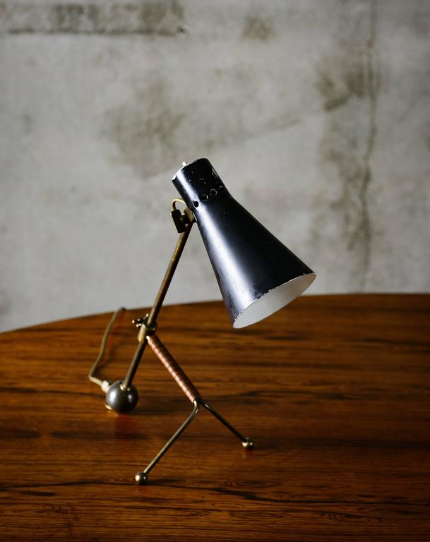 An icon of Scandinavian design the Tapio Wirkkala table lamp boasts tubular brass with enameled aluminum. Produced by Idman, Model K11-16, Finland, 1958. The lamp is in good condition with minor scratches on shade. Vintage.