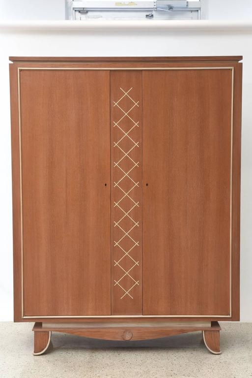 This French modern limed oak and parchment tall cabinet by designer Pierre Petit was made in the 1940s. The cabinet stands on raised carved legs with interlacing frieze in the centre. It has 2 doors with inlaid parchment in a cross hatched pattern