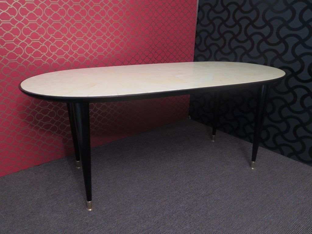 Italian Art Deco table. Top all covered in parchment leather with large edge in black lacquered wood. Note the design that forms the parchment leather on the top, two large central ovals then all around again pieces as if it were sunlight. The body