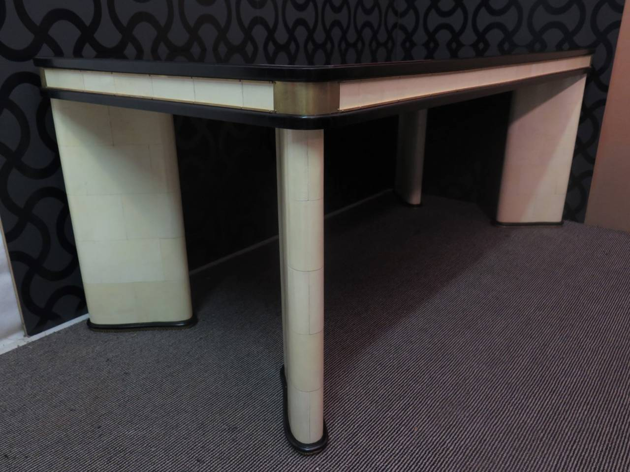 Italian Art Deco table. Composed of three materials, wooden structure then glass and parchment leather. The tabletop is covered by a black glass embedded inside, well rounded on the corners and has a black lacquer frame that runs all around the edge