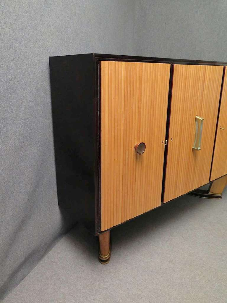 High sideboard of the Borsani Atelier of Varedo. High quality finishes for this sideboard. Body all in black lacquer, with three well-worked front doors. Note its workmanship with ribs in half-round maple. Two doors, right and left, have the key to