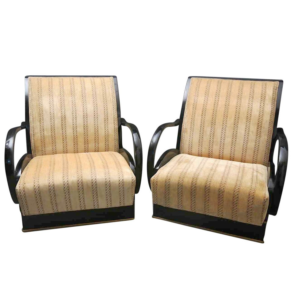 Pair of Italian Art Deco armchairs. All veneered in walnut wood. Particular the armrests, that from the design to comma are polished in black lacquer. Also the seat are covered in light brown velvet. The very high and wide backrest is veneered in