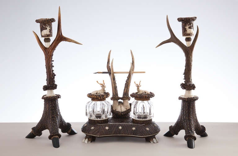The inkwell has a pen rest in roe deer horn and the base is in layered stag horn with star decoration, the two inkwells have lids both surmounted with carved stags.
