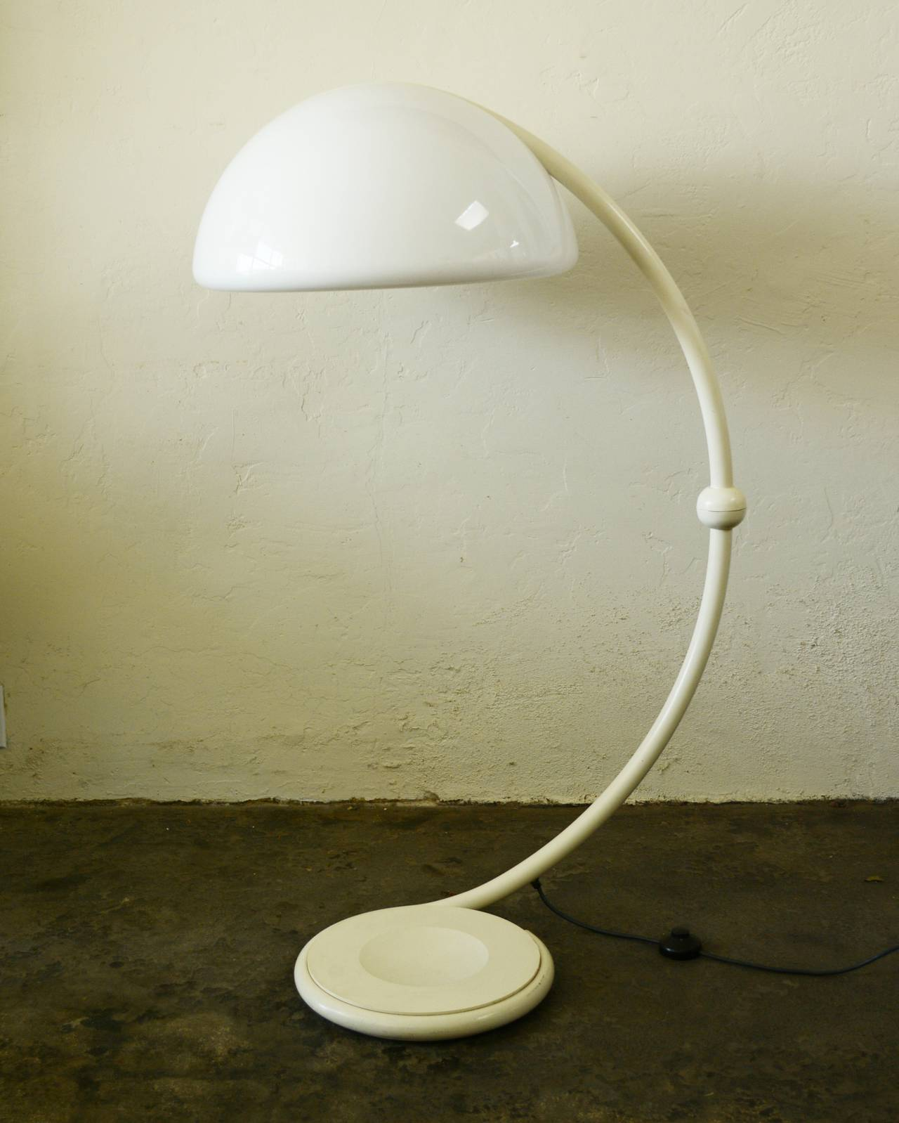 Classic lamp design by Elio Martinelli. The top half of this lamp pivots 360 degrees creating many different looks. This has some wear in spots to the paint and one touched up spot. The acrylic shade has minor wear and a couple of small deeper